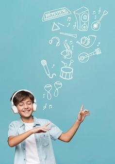Garoto de tiro médio usando fones de ouvido