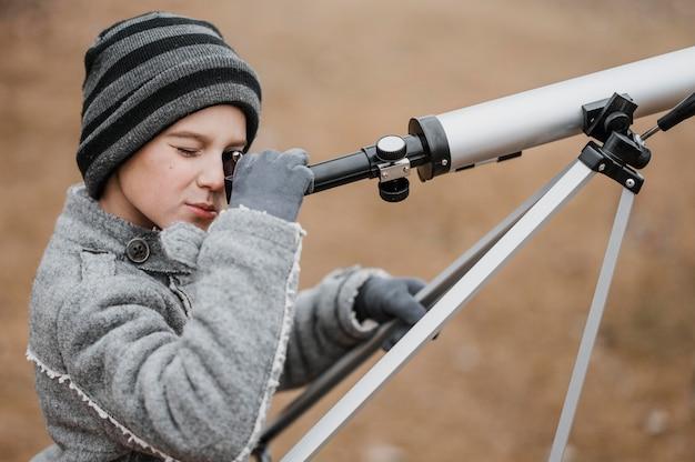 Garoto de visão lateral usando um telescópio