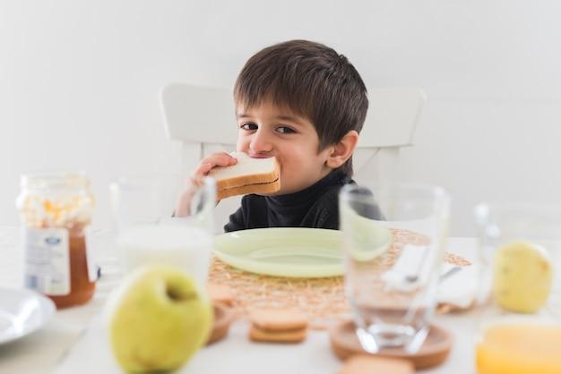 Garoto de vista frontal comendo sanduíche na mesa