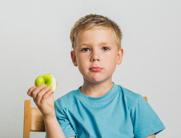 Garoto de vista frontal em uma cadeira com uma maçã