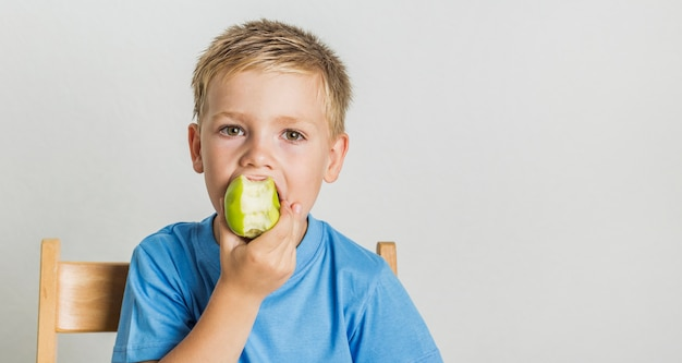Garoto de vista frontal mordendo uma maçã verde