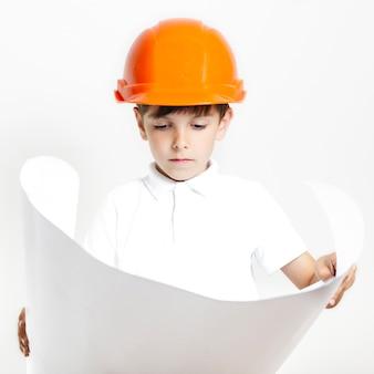 Garoto de vista frontal olhando planos de construções de introdução