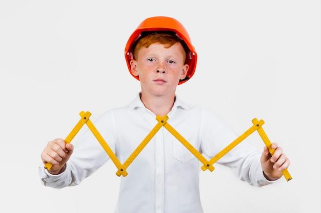 Garoto de vista frontal posando como trabalhador da construção civil