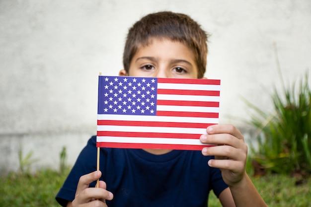 Garoto de vista frontal, segurando a bandeira dos eua