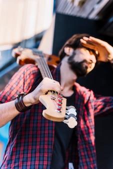 Garoto de vista inferior segurando a guitarra elétrica