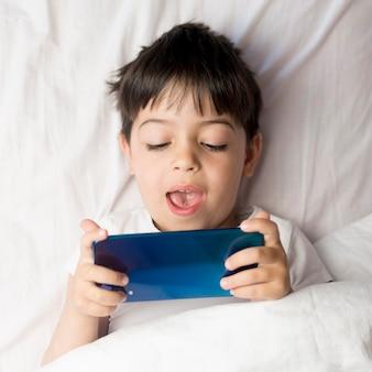 Garoto de vista superior com telefone na cama