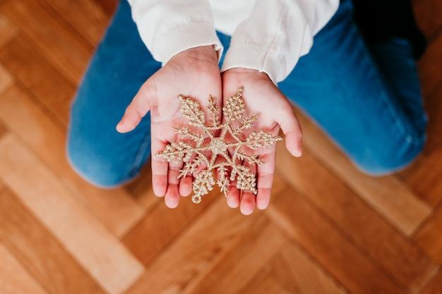 Garoto decorando a árvore de natal em casa. segurando um floco de neve dourada