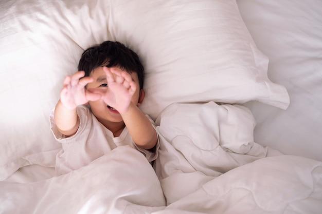Garoto deitado jogando e sorrindo na cama branca com travesseiro e cobertor