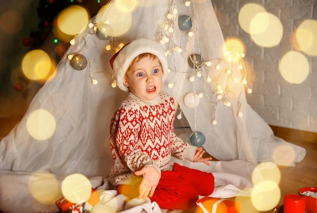 Garoto desempacota presentes embaixo da árvore de natal. garoto bonito com chapéu de papai noel