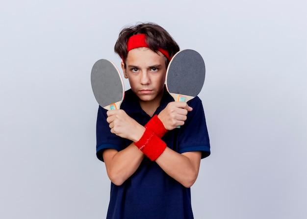 Garoto desportivo jovem confiante usando bandana e pulseiras com aparelho dentário, de mãos cruzadas, segurando raquetes de pingue-pongue, olhando para a câmera, isolada no fundo branco com espaço de cópia