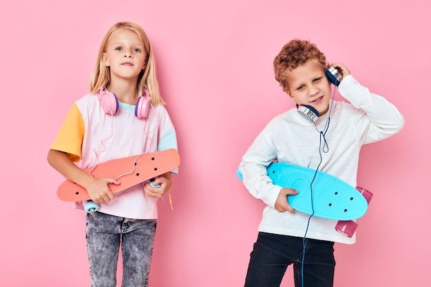 Garoto e garota bonitos segurando skates entretenimento fones de ouvido música