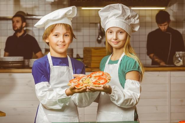 Garoto e garota chef felizes cozinhando na cozinha do restaurante