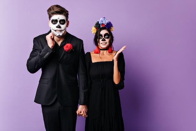 Garoto e garota com rostos pintados estão envergonhados, posando no estúdio roxo. homem e mulher dão as mãos.