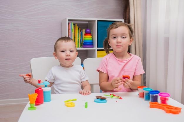 Garoto e garota engraçados brincam de brincadeira na mesa do quarto das crianças