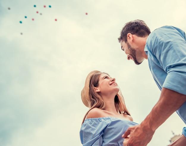 Garoto e garota estão se olhando e sorrindo. casal jovem alegre está olhando um ao outro e eles estão felizes.