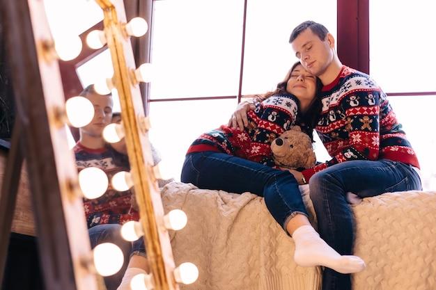 Garoto e garota fecharam os olhos e sentaram-se no espelho do peitoril da janela com lâmpadas refletidas
