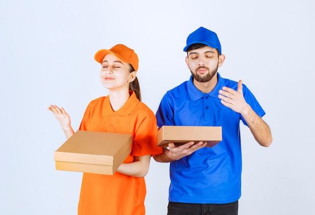 Garoto e garota mensageiro em uniformes azuis e amarelos segurando caixas de papelão para viagem e pacotes de compras e cheirando a comida.
