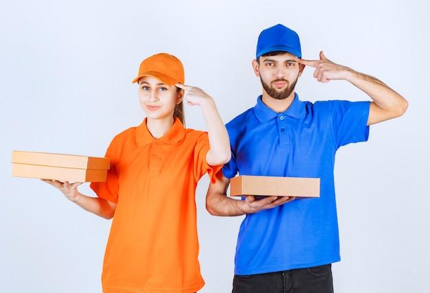 Garoto e garota mensageiro em uniformes azuis e amarelos segurando caixas de papelão para viagem e pacotes de compras parecem confusos e pensando em novas idéias.