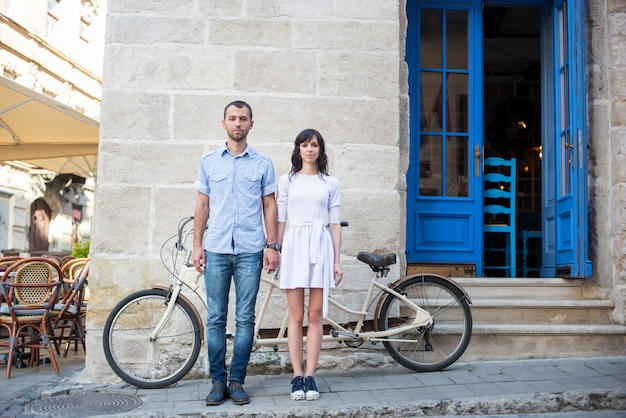 Garoto e garota perto de bicicleta tandem, paredes e porta vintage