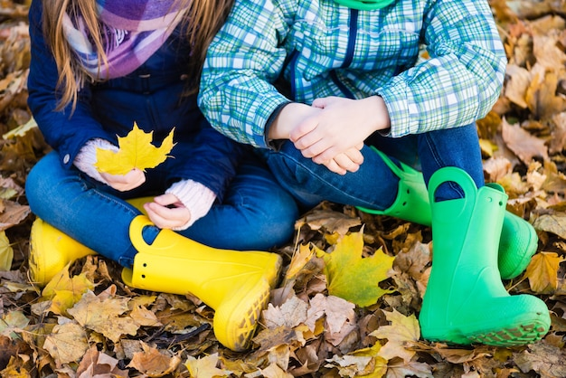 Garoto e garota pré-adolescente andando com sapatos de chuva brilhantes