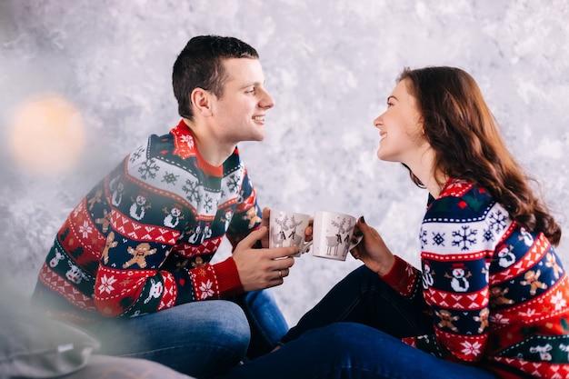 Garoto e garota sentados segurando um copo com bebida quente e olhando um para o outro
