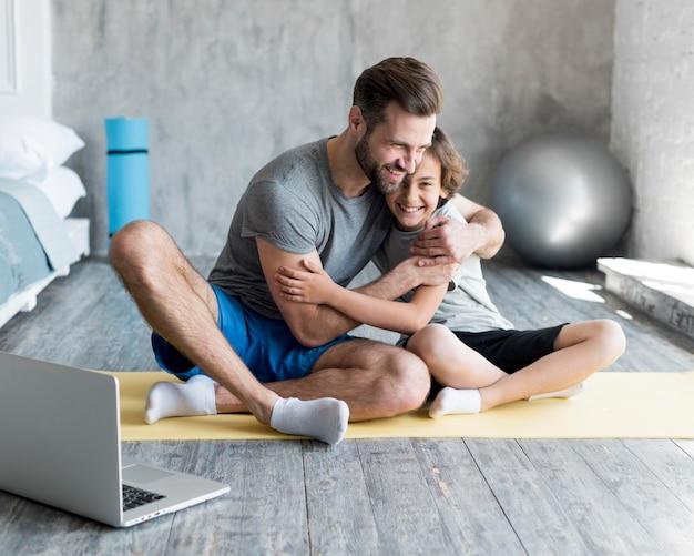 Garoto e seu pai fazendo esporte em casa