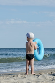 Garoto em calção de banho com um círculo de natação fica na costa do mar de volta
