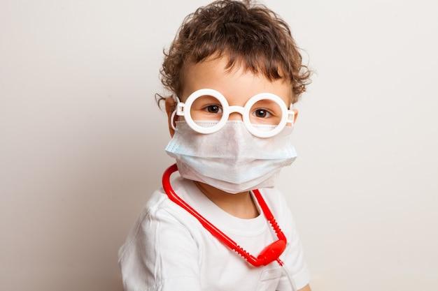 Garoto encaracolado engraçado em uma máscara médica e óculos. retrato maior de uma criança que exerce a profissão de médico.
