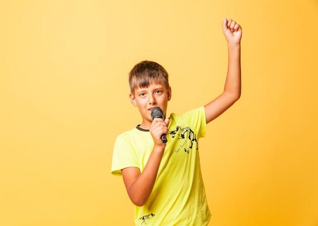 Garoto engraçado cantando com microfone em fundo amarelo