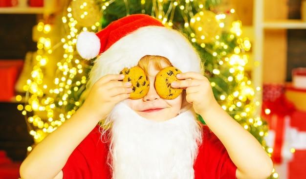 Garoto engraçado cobrindo os olhos com biscoitos