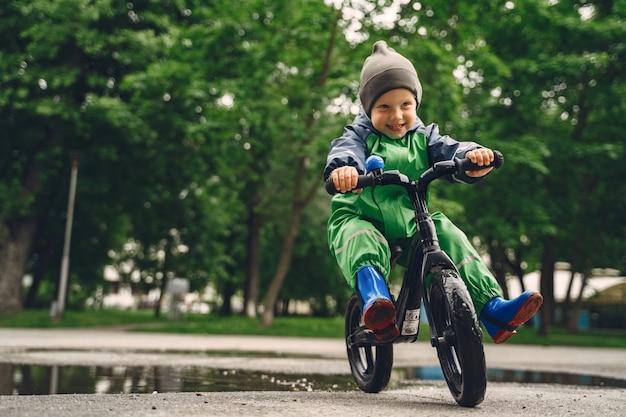 Garoto engraçado com botas de chuva brincando em um parque de chuva