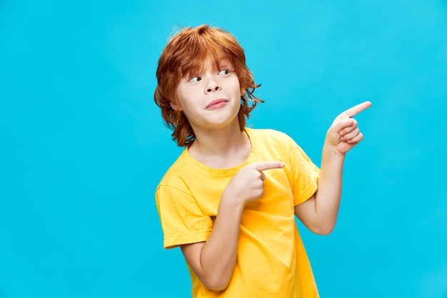 Garoto engraçado com cabelo vermelho mostra o polegar para o lado