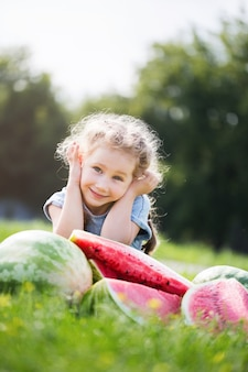 Garoto engraçado comendo melancia ao ar livre no parque de verão.