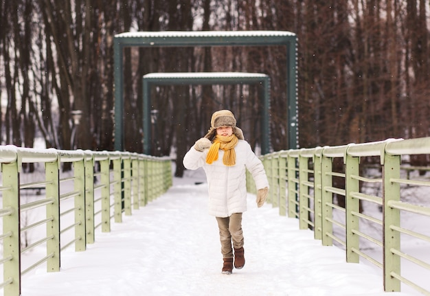 Garoto engraçado corre pelo parque no inverno e se diverte