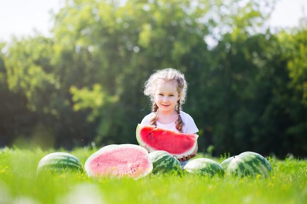 Garoto engraçado e melancia ao ar livre no parque de verão. criança, comida saudável.