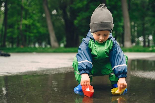 Garoto engraçado em botas de chuva, jogando em um parque de chuva