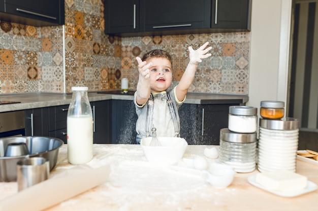 Garoto engraçado em pé em uma cozinha roustic brincando com farinha qe jogando-a para o ar.