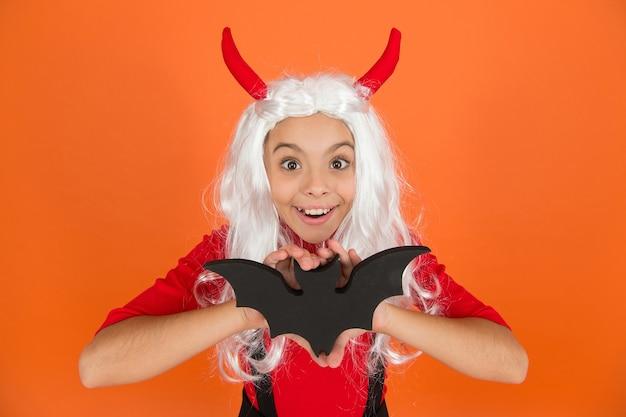 Garoto engraçado no chapéu da fantasia de bruxa para o halloween com hors de diabo e peruca segurando o bastão em fundo laranja, monstros de halloween.