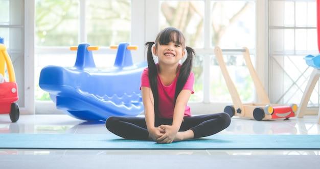 Garoto engraçado se divertindo após o exercício no quarto de crianças