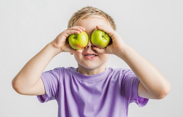 Garoto engraçado segurando maçãs verdes