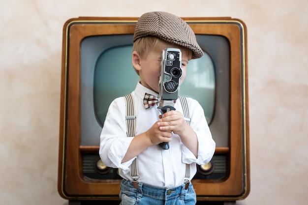 Garoto engraçado segurando uma câmera vintage. criança feliz se divertindo em casa. conceito de cinema retro