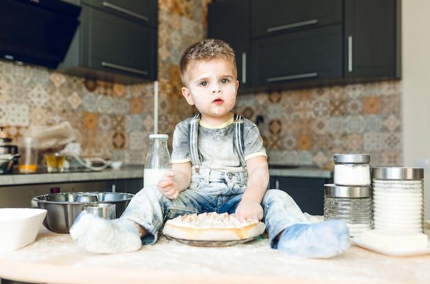 Garoto engraçado sentado na mesa da cozinha em uma cozinha roustic brincando com farinha e degustando um bolo.