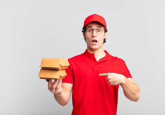 Garoto entregador de hambúrgueres parecendo chocado e surpreso com a boca aberta, apontando para si mesmo
