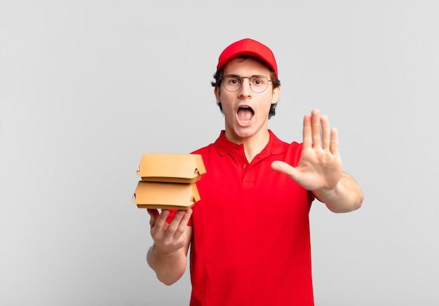 Garoto entregador de hambúrgueres parecendo sério, severo, descontente e irritado mostrando a palma da mão aberta fazendo gesto de pare