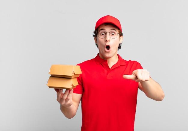 Garoto entregador de hambúrgueres parecendo surpreso em descrença, apontando para o objeto ao lado e dizendo uau, inacreditável