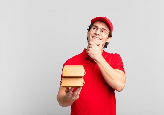 Garoto entregador de hambúrgueres sorrindo feliz e sonhando acordado ou duvidando, olhando para o lado