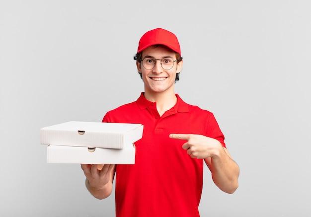 Garoto entregador de pizza se sentindo feliz, surpreso e orgulhoso, apontando para si mesmo com um olhar animado e surpreso