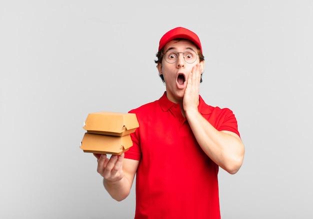 Garoto entregando hambúrgueres chocado e assustado, parecendo apavorado com a boca aberta e as mãos no rosto