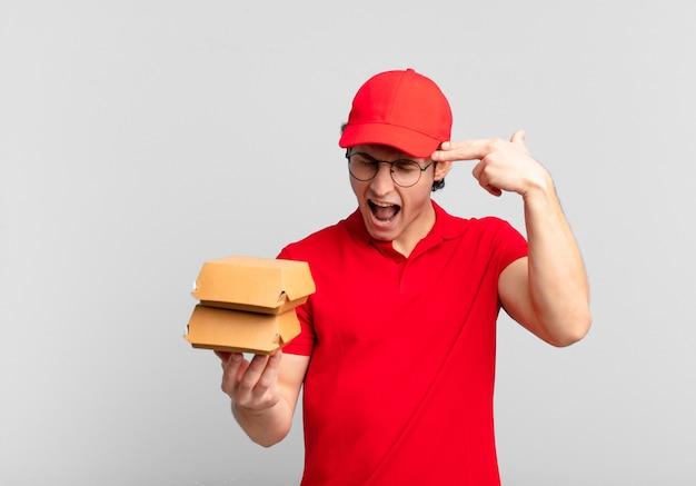 Garoto entregando hambúrgueres parecendo infeliz e estressado, gesto suicida fazendo sinal de arma com a mão, apontando para a cabeça
