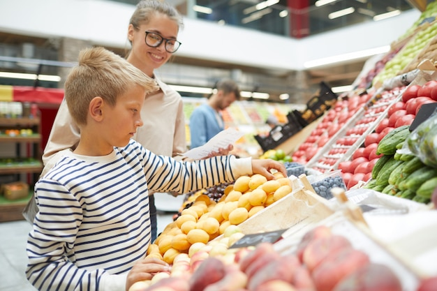 Garoto escolhendo frutas no supermercado